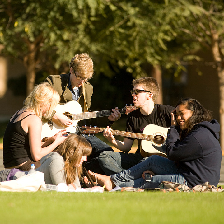 Music students playing guitars and doing homework in Sunken Garden