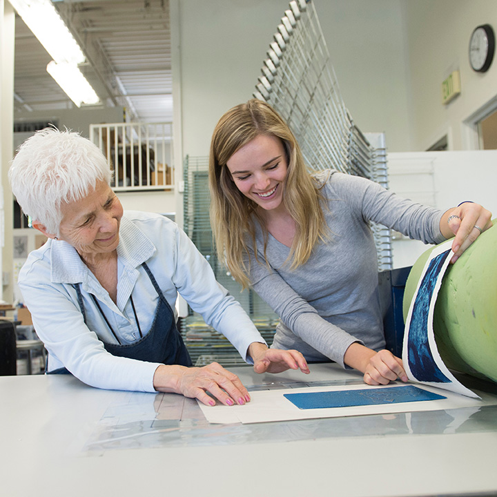 A printmaking professor and student working on a project together